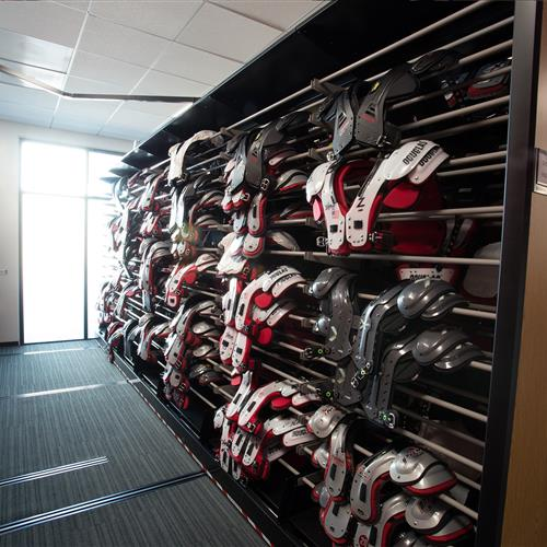 Athletic equipment of shoulder pads stored on powered mobile shelving at Stanford University