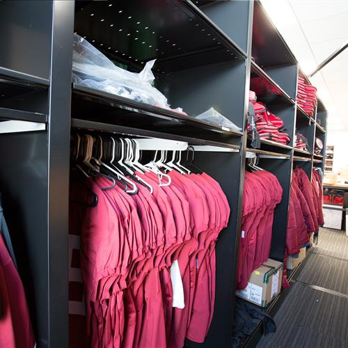 Hanging athletic uniforms on metal shelving at Stanford University