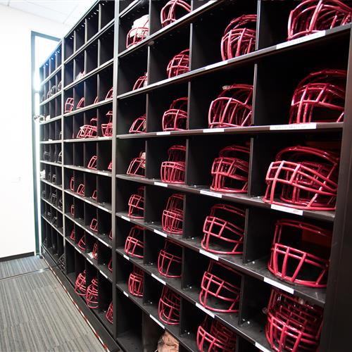 Face mask storage in bins on mobile shelving in athletic equipment room at Stanford University