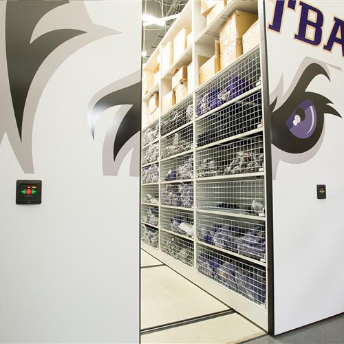 Athletic equipment stored in retractable wire basket shelving on powered compact mobile storage