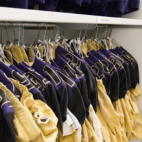 Jerseys athletic equipment stored on large 4-post shelving with hanging rod