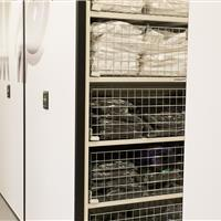 Athletic shirt storage in wire baskets on powered compact mobile shelving