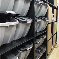 athletic equipment stored in totes on static shelving