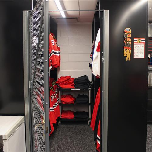 Athletic equipment stored in static gated shelving at Chicago Blackhawks Equipment Room