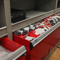 Athletic equipment stored in modular drawers and shelving