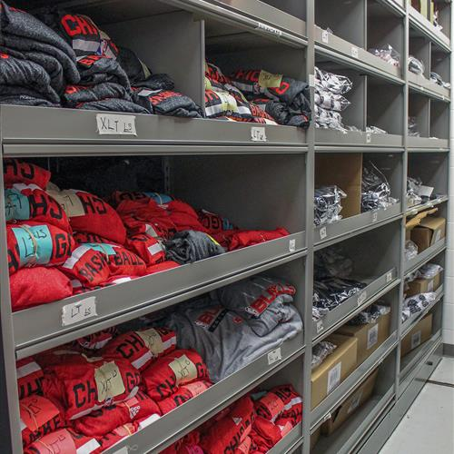 Bin storage on static shelving for athletic apparel at the Chicago Bulls Equipment room
