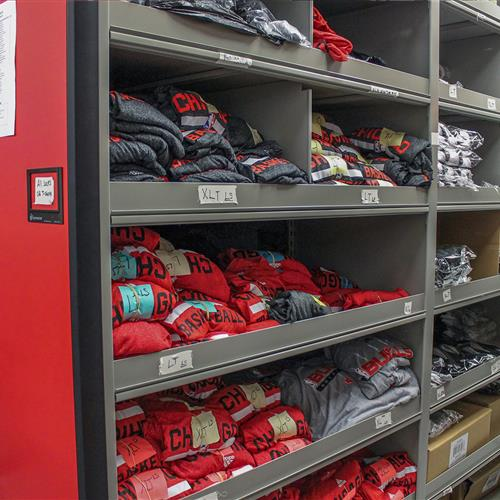 Athletic apparel stored on compact mobile shelving