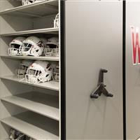 Athletic equipment of helmet and chin strap storage on mechanical assist compact mobile shelving