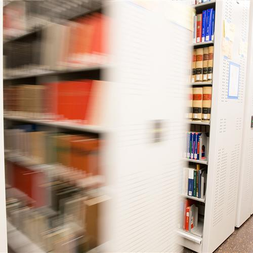 Compact mobile shelving in motion to access library books