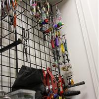 Carabiners and climbing equipment on hanging storage racks between shelving units