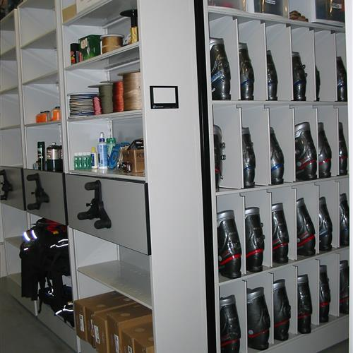 Ski boots and recreational supplies on compact mobile shelving