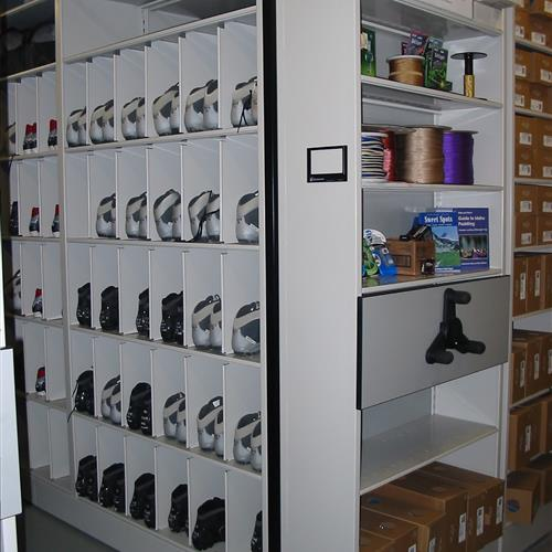 Climbing shoes separated by bins on compact mobile with easy access shelving on front of system