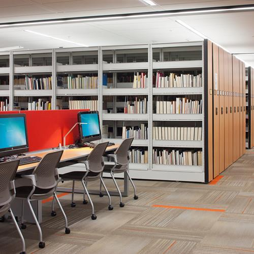 Compact mobile storage library shelving next to computer resource area