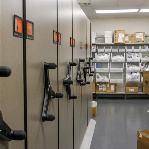 High-density mechanical assist mobile shelving and supplies on static bin shelving