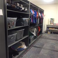 Athletic equipment on hanging racks and shelving