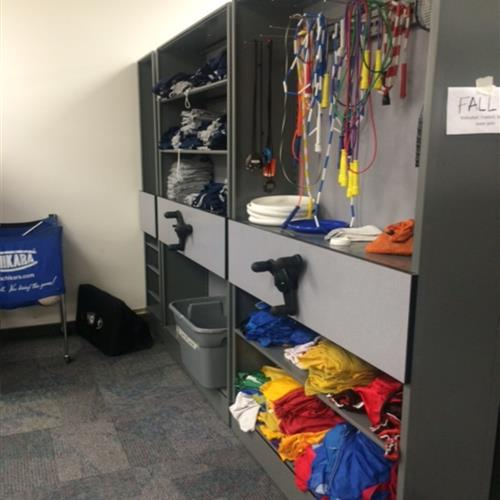 Athletic equipment storage on shelving and pegs