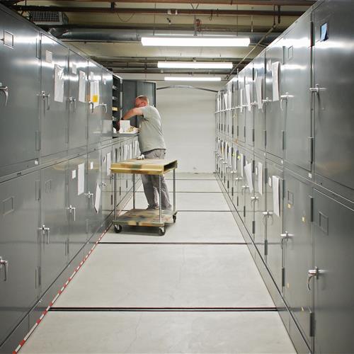 Paleontologist handling fossils inside of cabinet on a High Density Mobile System Raymond Alf Museum