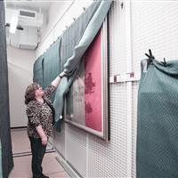 Wall mounted art racks protected by tambour doors