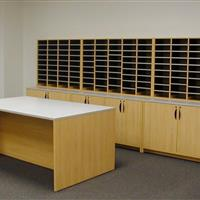 Wood finish mailroom storage with drawers, desk and more