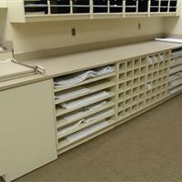 Close up of off white mailroom storage with drawers, cabinets and more