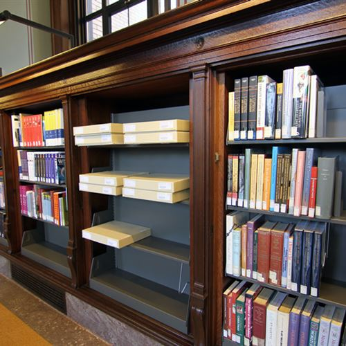 Metal library shelving retrofitted into builtin bookcase