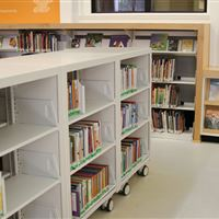 Multiple custom cantilever shelving on wheels to create continuous library storage unit